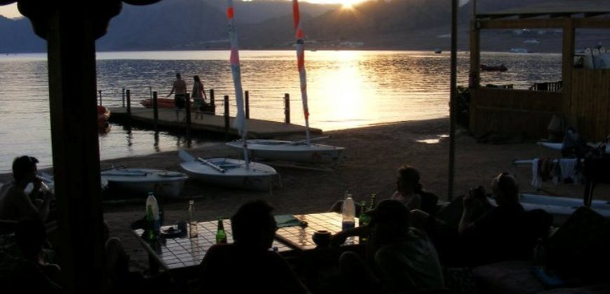 A group pf people having drinks at sunset, at the casual beach bar overlooking the bay