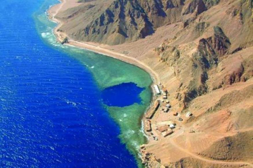 The blue hole from the air. A round hole in the coral reef by the coast. The coast is arid with a few buildings on the shore and the sea is perfectly bright blue