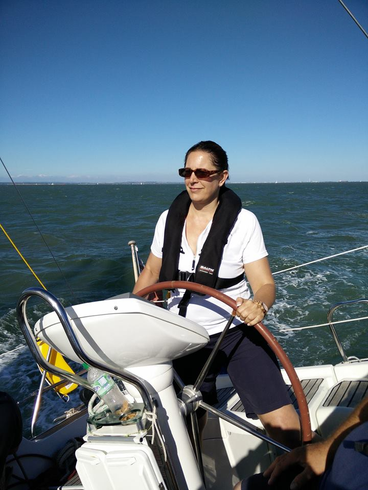 Me at the helm of a yacht wearing t shirt and shorts on a sunny summer day in the Solent