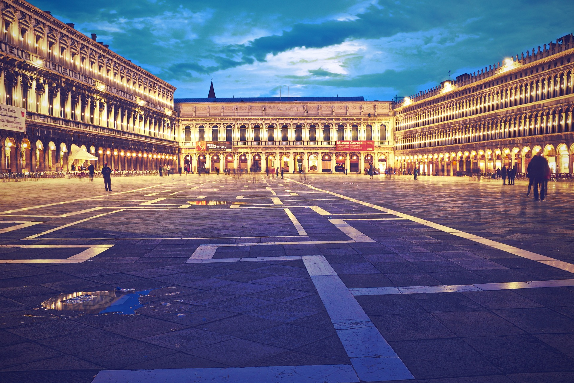 A large public square with patterned paving and surrounded by grand buildings fronted by columns and lit up against the early evening sky