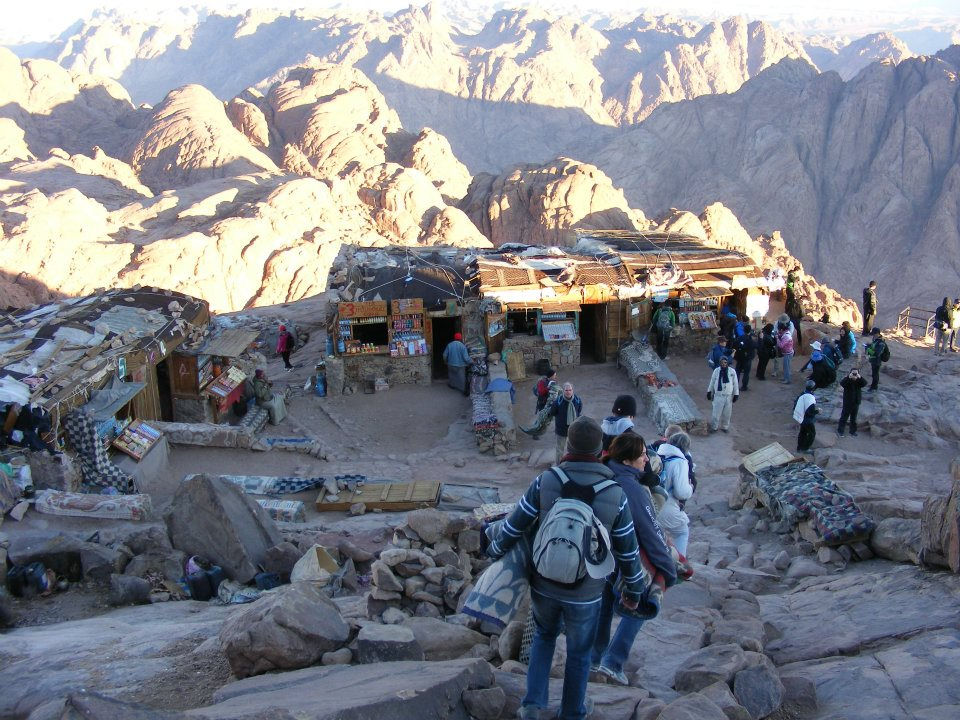 Ramshackle cafes near the top of the Sinai mountain at sunrise, with groups of walkers congregating. Sunlit rocky mountains are in the background