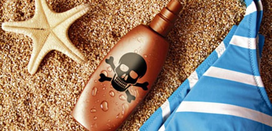 A bikini, shell and suncream bottle with a skull and crossbones on it, on the sand