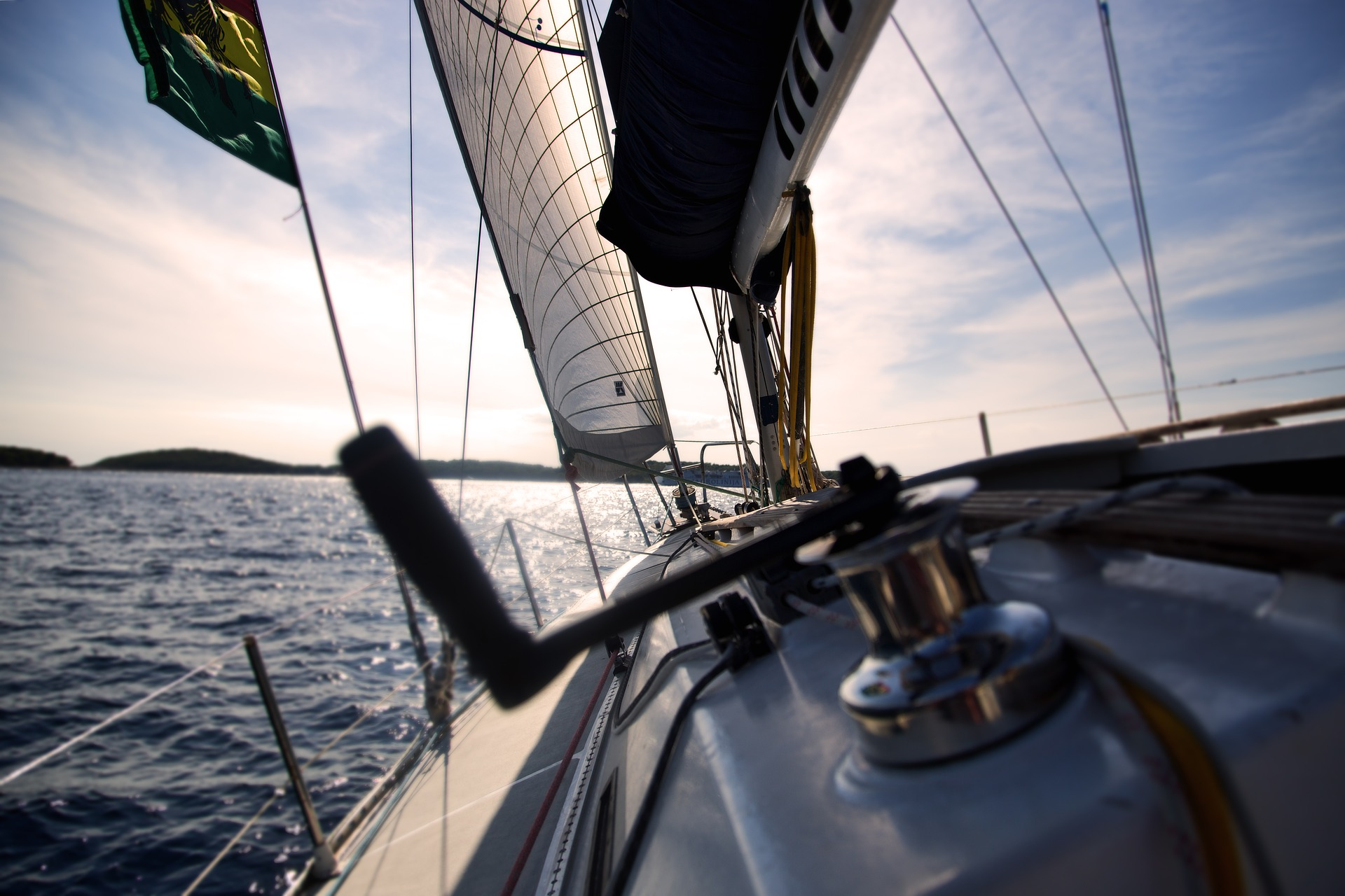View of a boat foredeck taken from the cockpit. The boat is under sail, over seas heading towards land