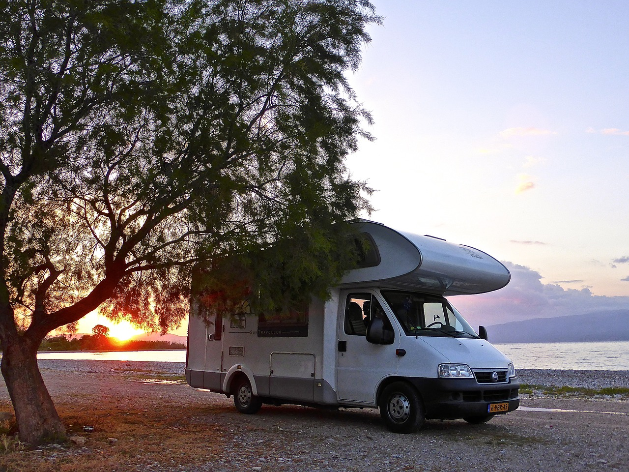A large campervan parked on a rocky shoreline at sunset