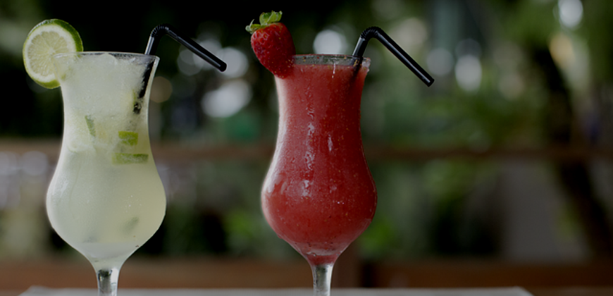 Two cocktails with fruit decorations and plastic straws