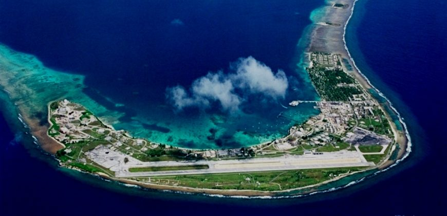An aerial view of Kwajalein, boomerang shaped, most of the island is taken up by a runway, with buildings and grass covering the rest. The island is surrounded by coral reef and beautiful bright blue seas