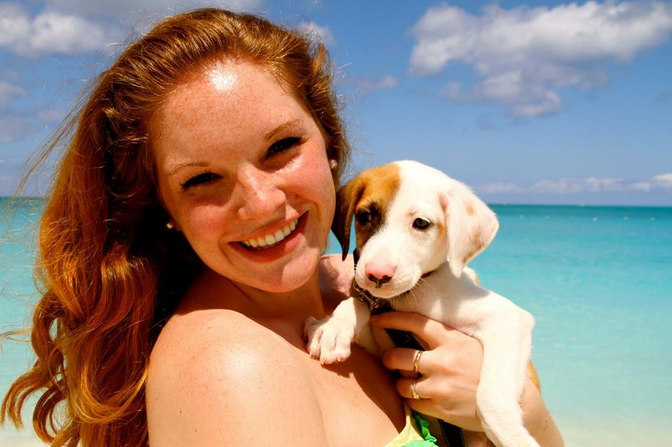 A stunning red haired girl holding a puppy with turquoise sea in the background and a light blue sky with a few fluffy white clouds.