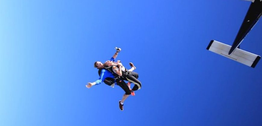Tandem skydivers having just jumped out of a plane, arms and legs spread
