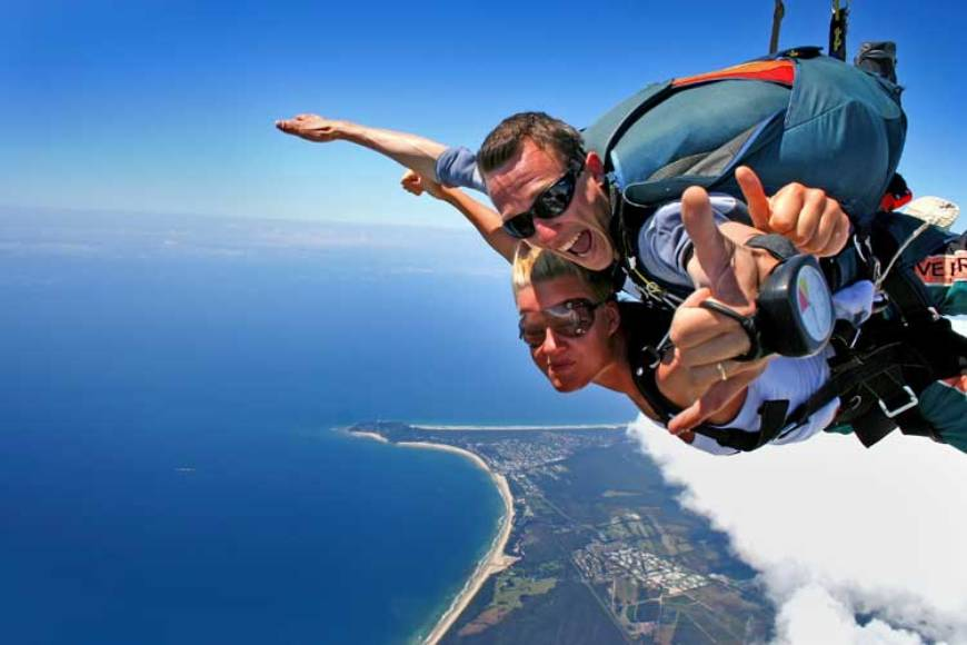 A man and woman tandem skydiving over a beautiful coastline