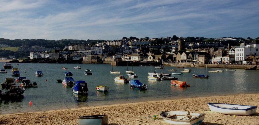 St Ives Harbour, taken from the sandy beach, there are small day boats on the sand and in the natural harbour, with the town in the background set against a blue sky with wispy clouds