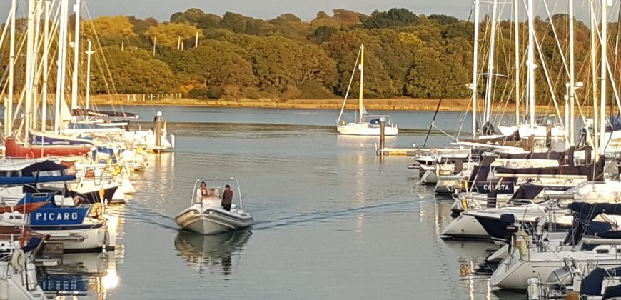 A motorboat cruising down a slipway leaving a gentle wake, with boats either side and lush green trees in the background on the other side of the river