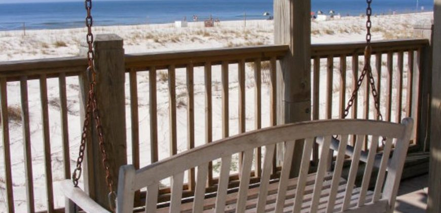 A white wooden porch swing overlooking the beach