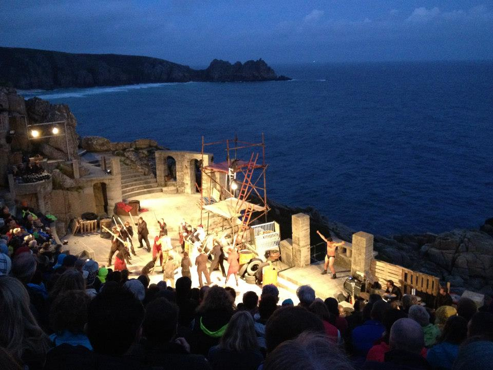 Minack Theatre mid performance, the stage is lit and the sea is visible in the distance