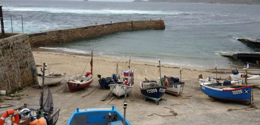Sennen Cove shoreline with fishing boats tied up on the beach and waves crashing in the background