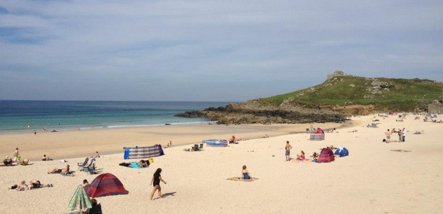 St Ives beach in the middle of the day, the sand is yellow, the water an array of blues and the sky blue with wispy clouds. In the background there is a green grassy hill and people are playing on the beach