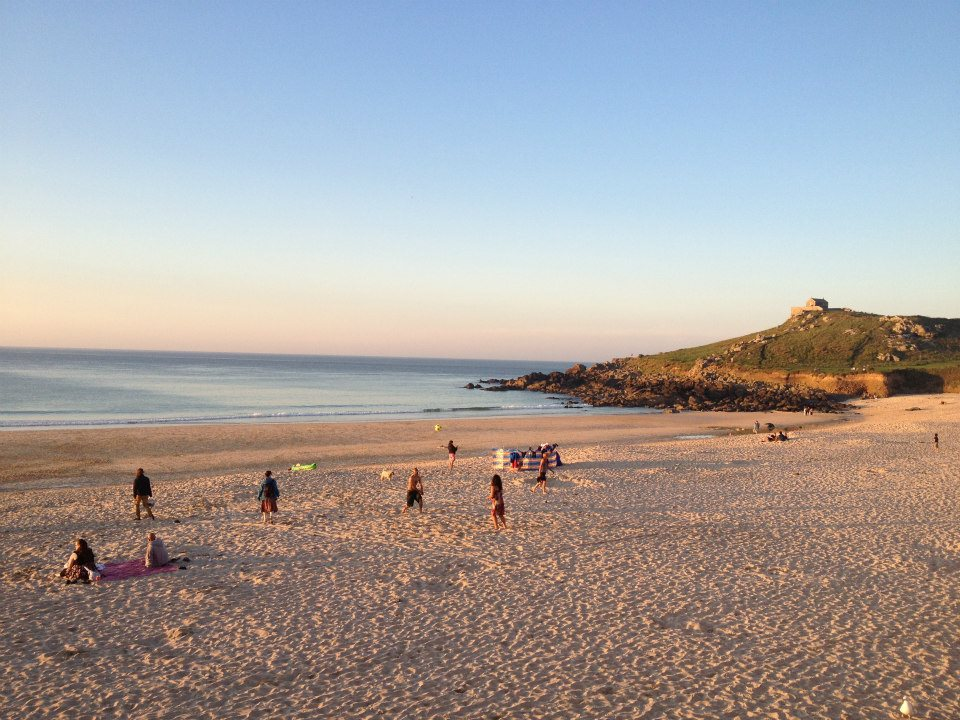 St Ives beach at sunset, the sand is pink, the water purple and the sky blue. In the background there is a green grassy hill and people are playing on the beach