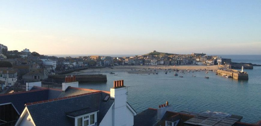 A view over St Ives harbour with cottage roofs in the foreground and the town in the background, taken late afternoon as the sun sets, the town looks golden and the sky is blue and pink