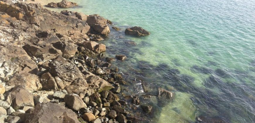 St Ives waterfront with rocks leading into clear seas on a sunny day