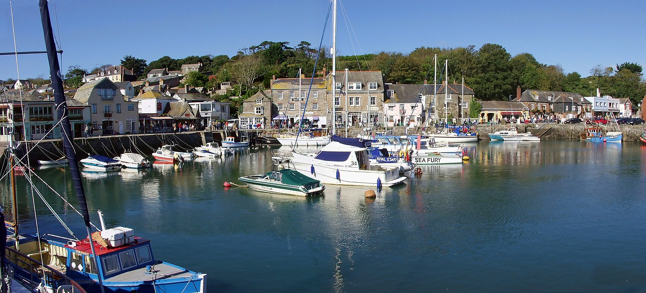 Padstow harbour, a natural harbour with day fishing boats moored up, against a backdrop of old stone Devon cottages, trees and blue skies