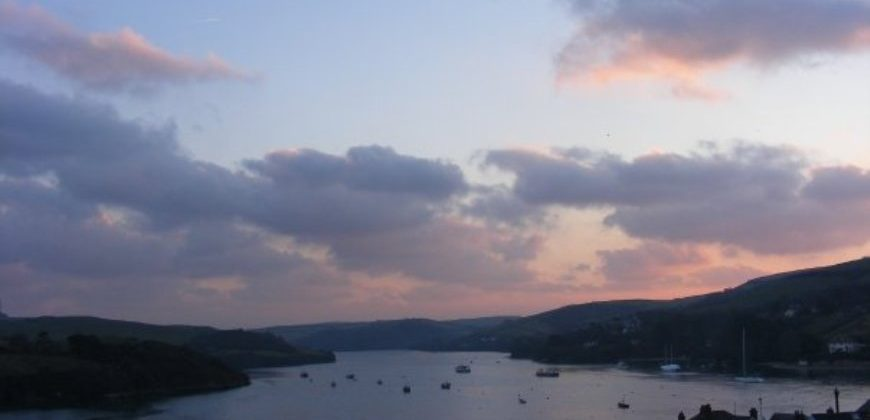 Salcome Bay after sunset. Taken from the hill overlooking the bay, there are Cornish cottages in the foreground and boats on the water in the background