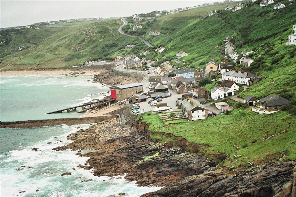 Sennen Cove, a tiny village of small Cornish cottages with a life boat station, surrounded by green hills and overlooking a craggy coastline
