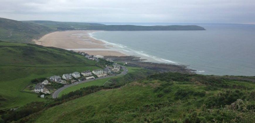 Woolacombe beach taken from the north, green hills and a huge beach with only one row of houses visible