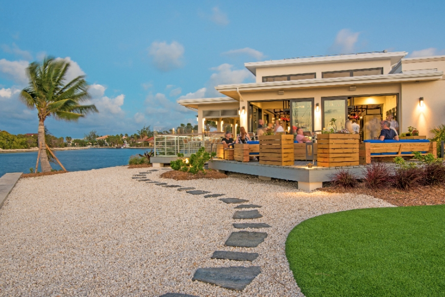 Cayman Bacaro restaurant terrace, with manicured lawns and gravel in the foreground, overlooking a canal with a palm tree