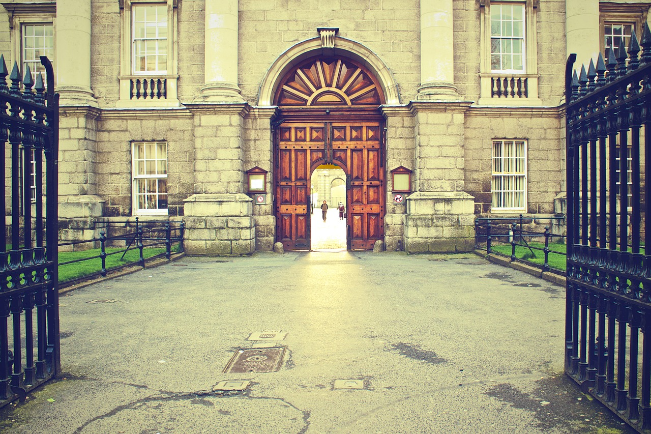 Trinity College, an old building made of light coloured large stones with a huge arched wooden doorway. In the foreground are large wrought iron gates