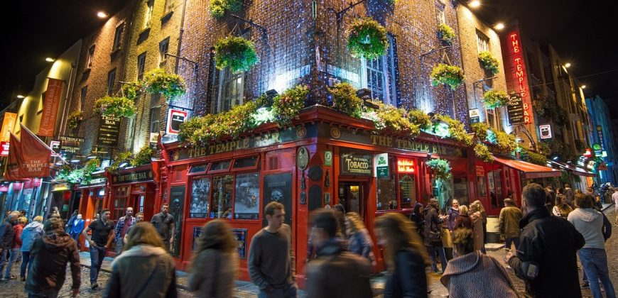 The Temple Bar at night. A busy street scene with crowds passing a red fronted pub covered in hanging baskets. It looks welcoming and atmospheric