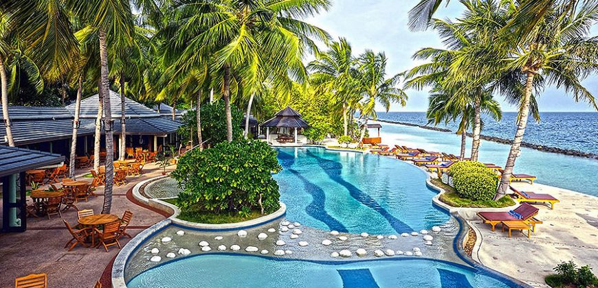 The swimming pools overlooking the sea, dotted with palm trees and sunbeds, with the restaurant behind