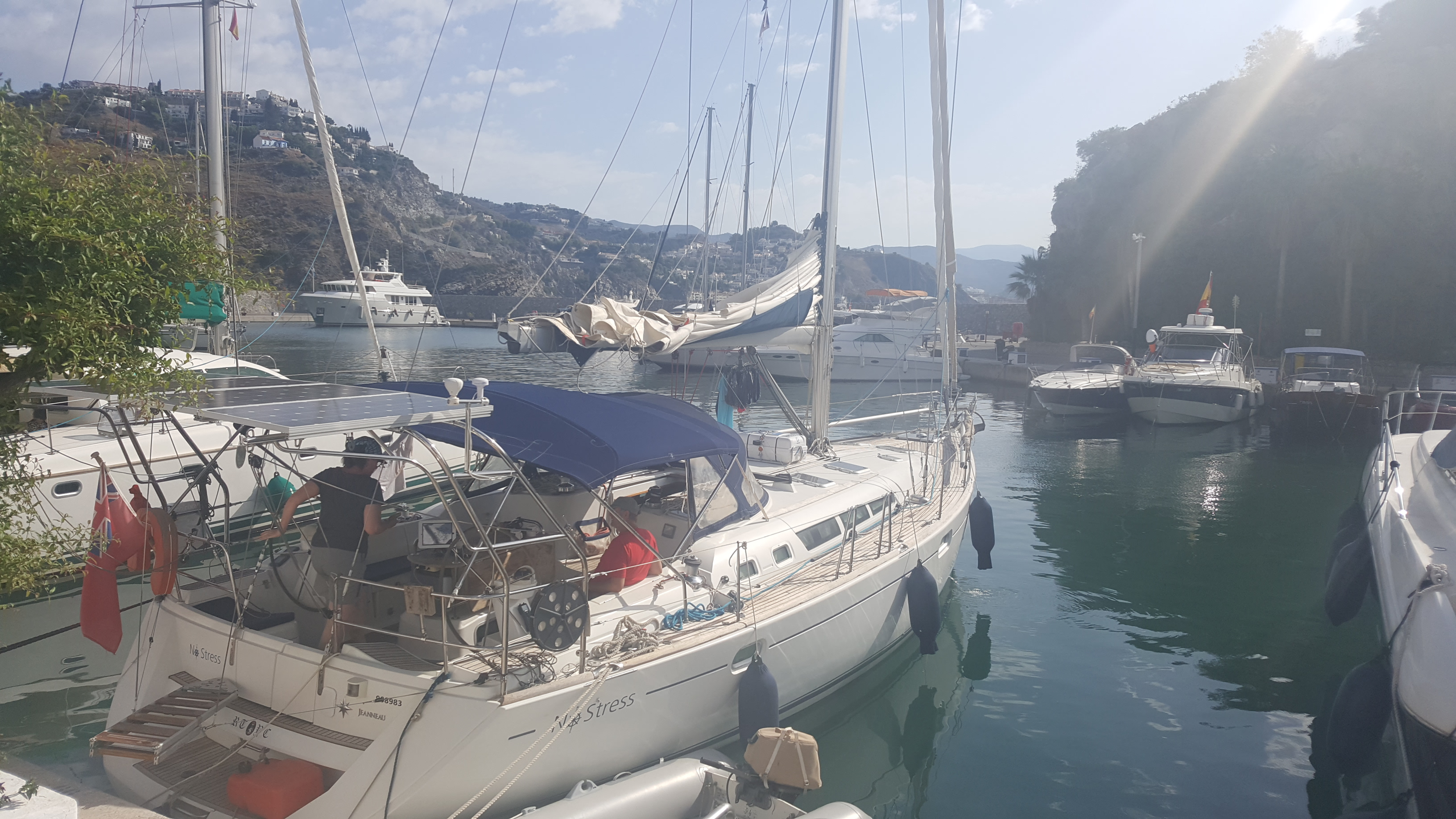 Our lovely yacht in Marina del Este, early morning, getting ready for a day at sea. The marina is surrounded by green hills, we have several boats around us and the sun is streaming down