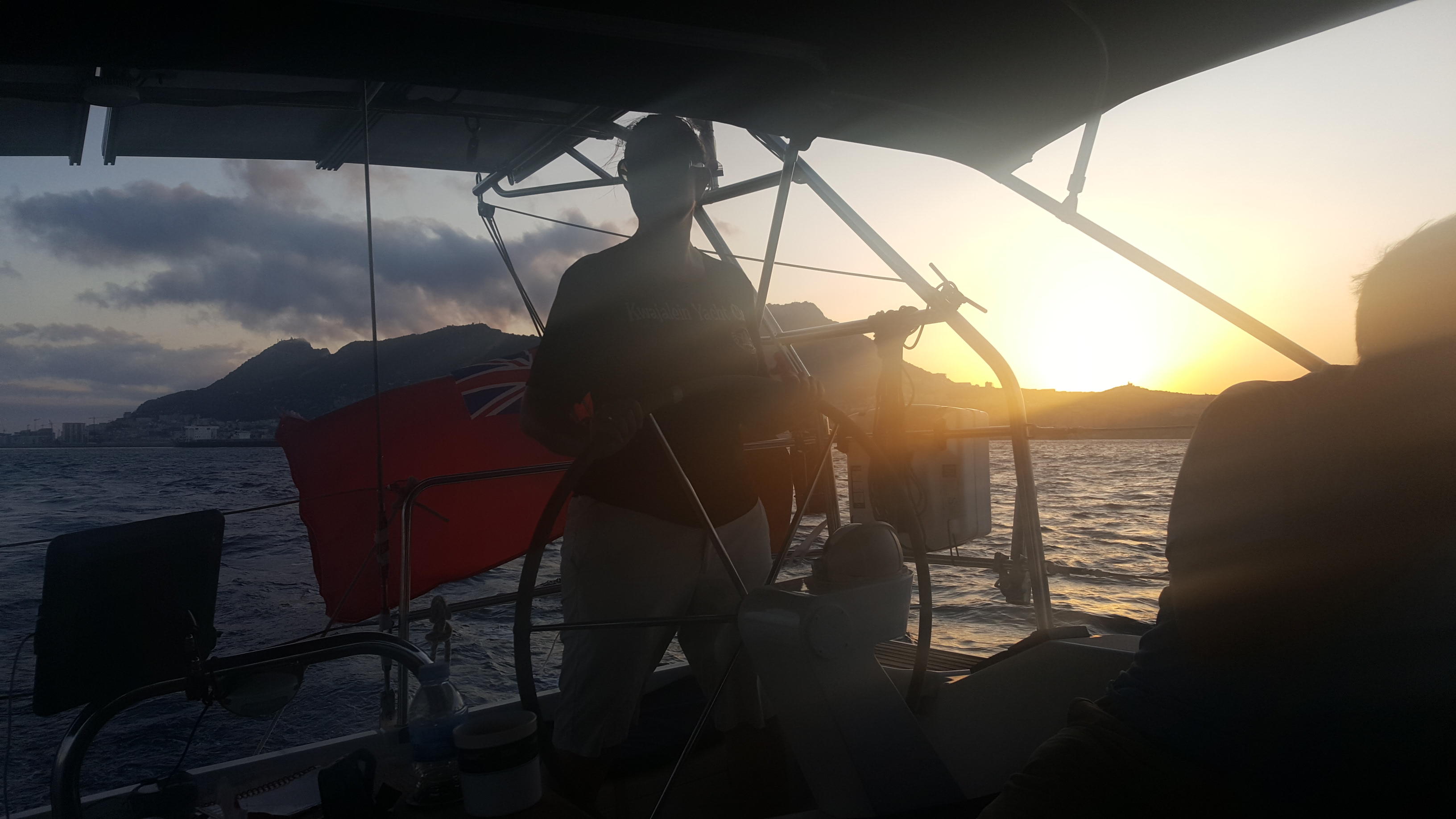Me at the helm as we round the rock of Gibralta. Our British ensign is flying and the sun is low in the sky, creating a silhouette