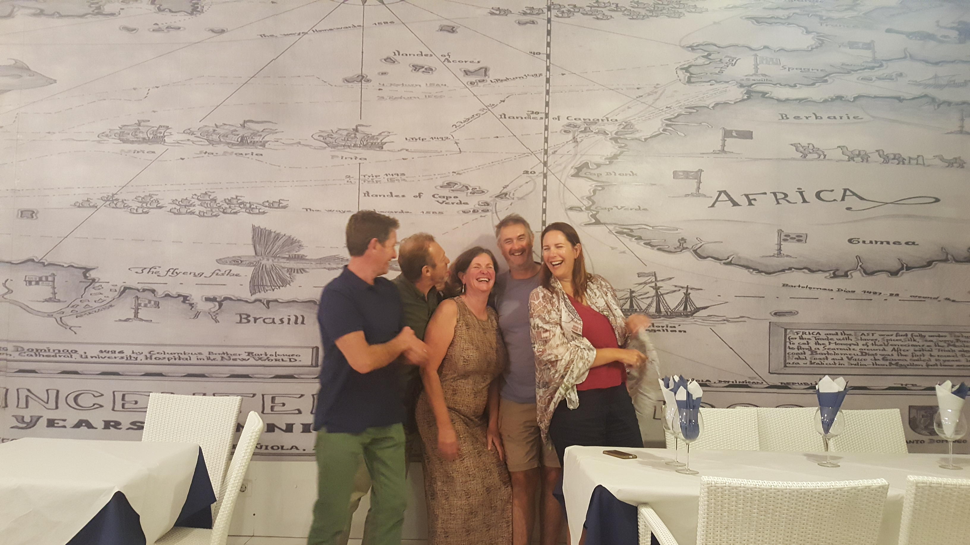 Team shot of the crew stood against a wall showing a map of Africa's west coast, we are all laughing