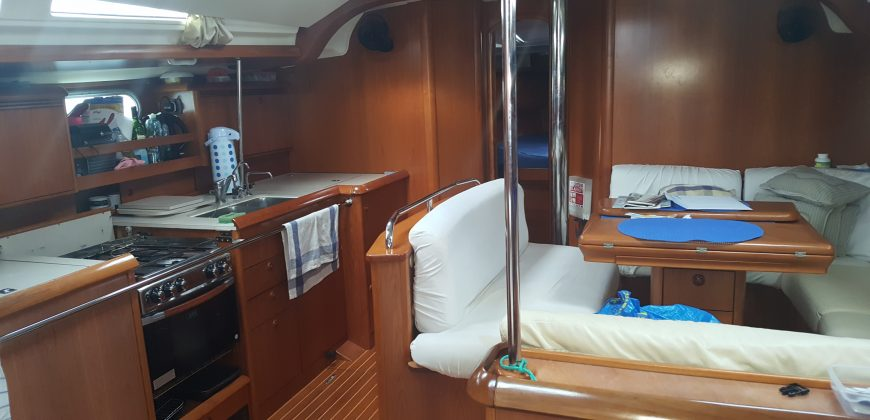 The saloon and galley of the boat, seating on the right and a long kitchen area on the left. MAde of wood, it is a clean, sociable space