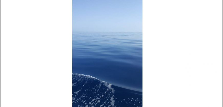 A small wave created by the boat, rippling against a flat calm medium blue sea, with a clear blue sky in the background