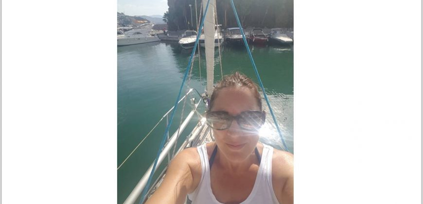 A picture of me early on a beautiful sunny morning, on the foredeck of the boat in the marina, with other boats int he distance. I'm wearing sunglasses and a vest top and have a suntan.