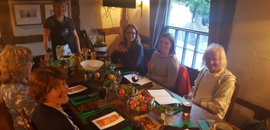 Our group introducing ourselves, We are sat at a table set with chopping boards, knives, aprons and recipe cards. Our teacher is at the head of the table. Lots of smiling faces!
