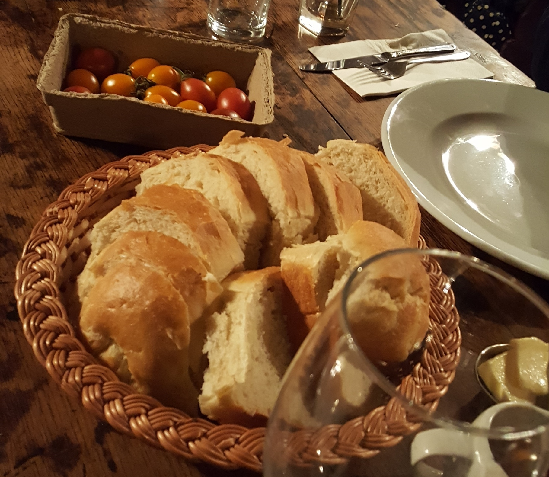 Fresh cut bread in a basket with a cardboard punnet of cherry tomatoes sad amidst place settings and a wine glass