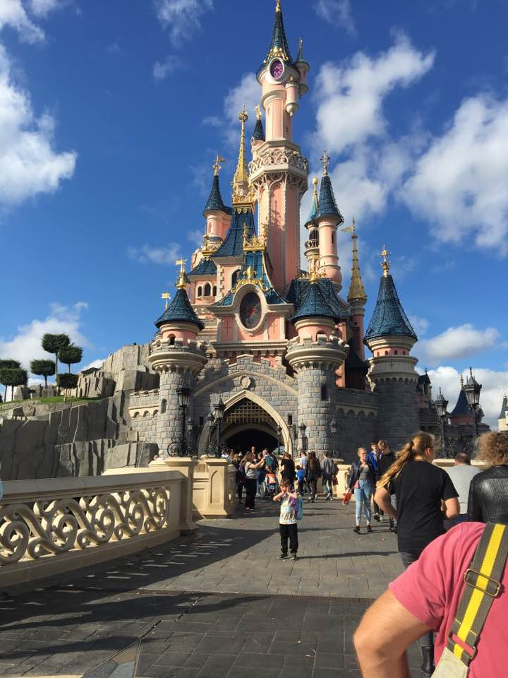 The iconic Disney castle, a collection of ever increasingly tall turrets in pink and blue, with an ornate bridge leading up to it