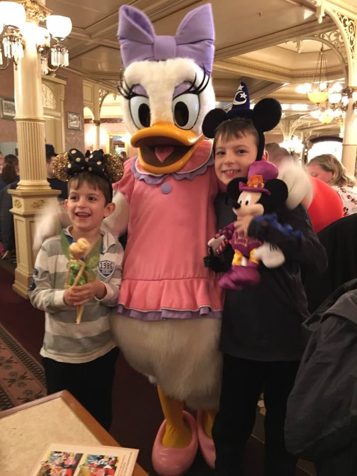 Ryan and Harvey posing with Daisy Duck, they are both wearing their Disney ears and holding Disney toys They both look very happy!