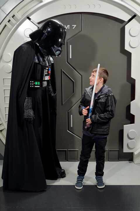 Ryan facing off to Darth Vadar. Darth is looking down at Ryan who is holding a light saber and looking back at him with a smile - not much scares Ryan!