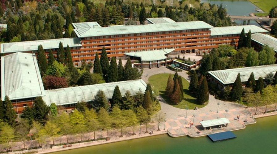 Sequoia Lodge hotel at Disneyland Paris. A large plain hotel surrounded by evergreen trees, overlooking a lake