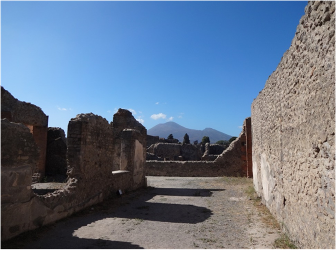 The ruins of Pompei. the remains of stone walls and floors, with mountains and blue skies in the background