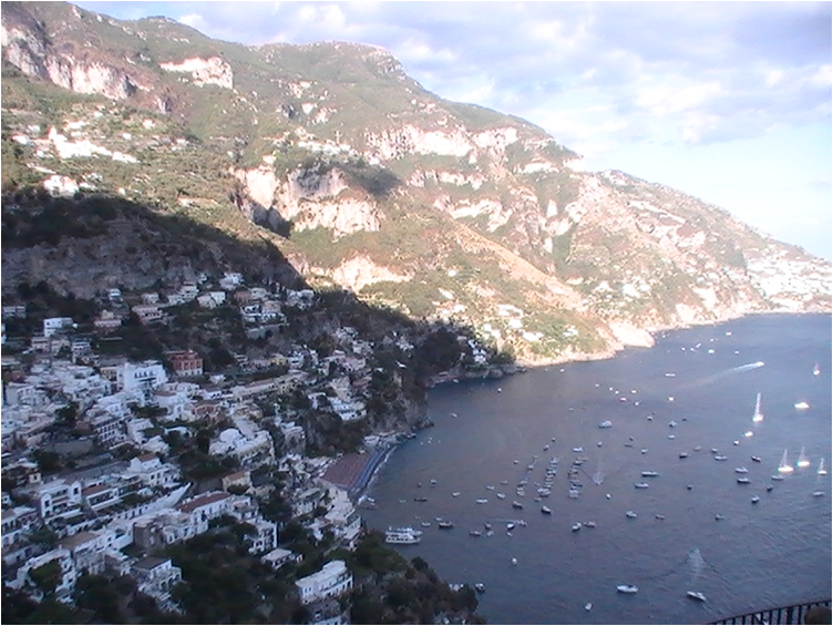 A view of Positano from up high. White houses on hillsides, some in the shade, some in the sun. Overlooking the sea dotted with boats