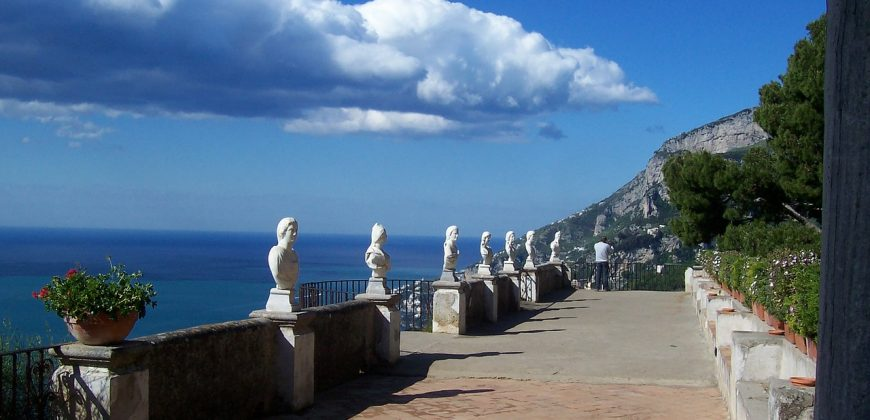 Sorrento boardwalk with a wall featuring statue busts, overlooking a beautiful blue sea on one side and lush green trees on the other side, A ribbon of cloud hugs the coastline but mostly the sky is clear blue
