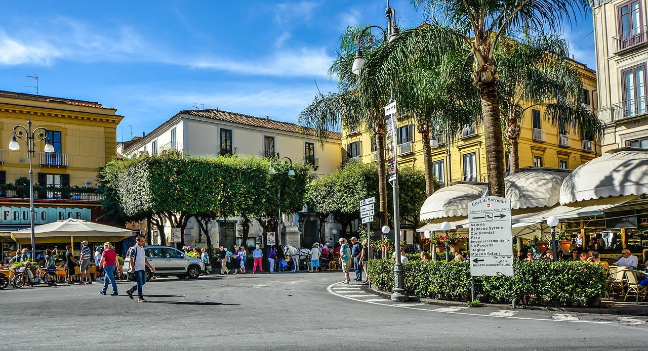 Sorrento Square. A crossroads bordered with beautiful Italian villas, restaurants and trees, with pedestrians bustling around