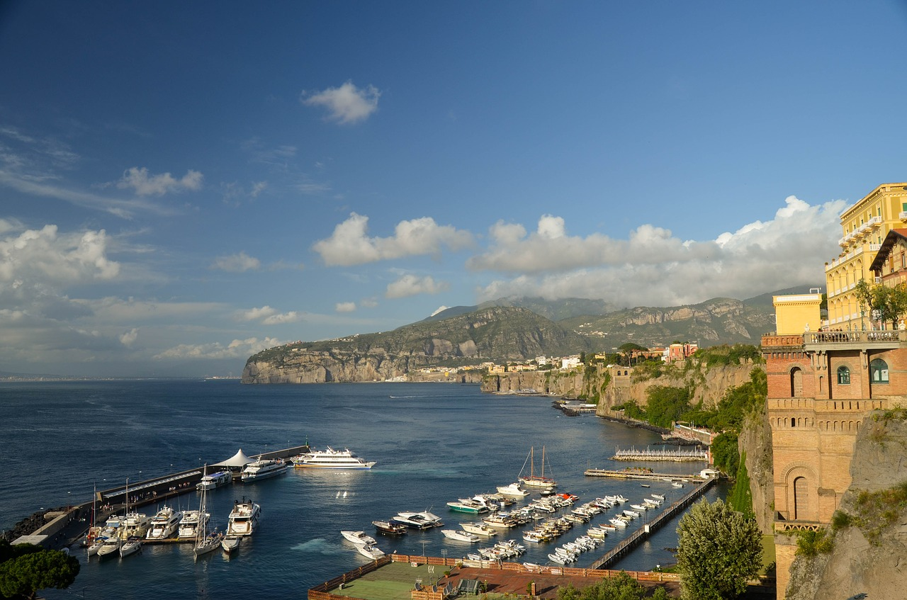 View of Sorrento marina with sail and motor boats parked up, rugged coastline in the distance and old Italian villas in the foreground