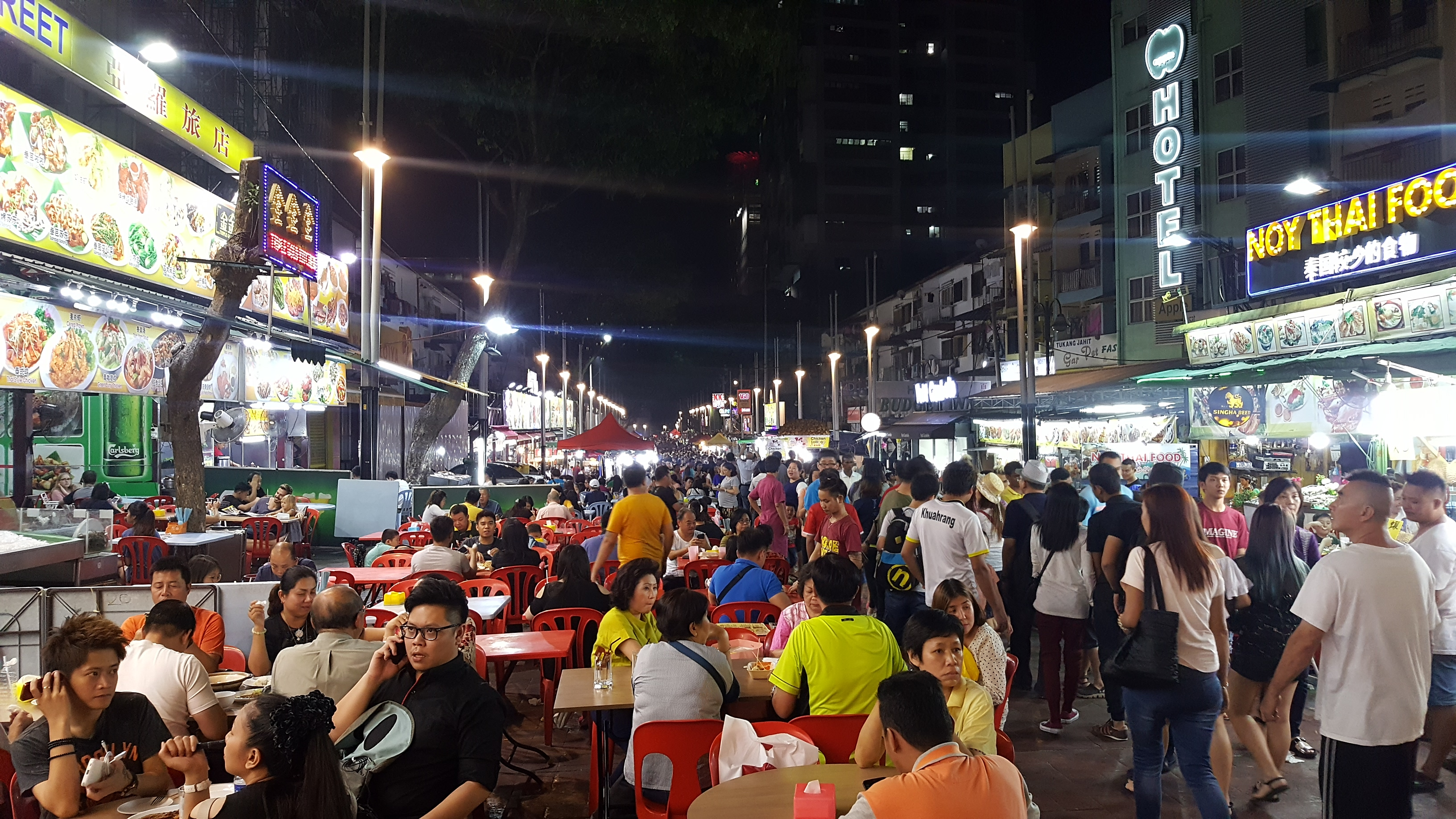 Jalan Alor street food market at night. Tables with people eating on the left, crowds walking past restaurants and food stands on the right. It looks simple. but colourful and lively