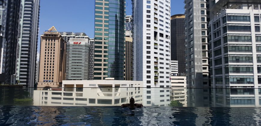 Me floating at the edge of the roof top infinity pool, with a city skyline in the background
