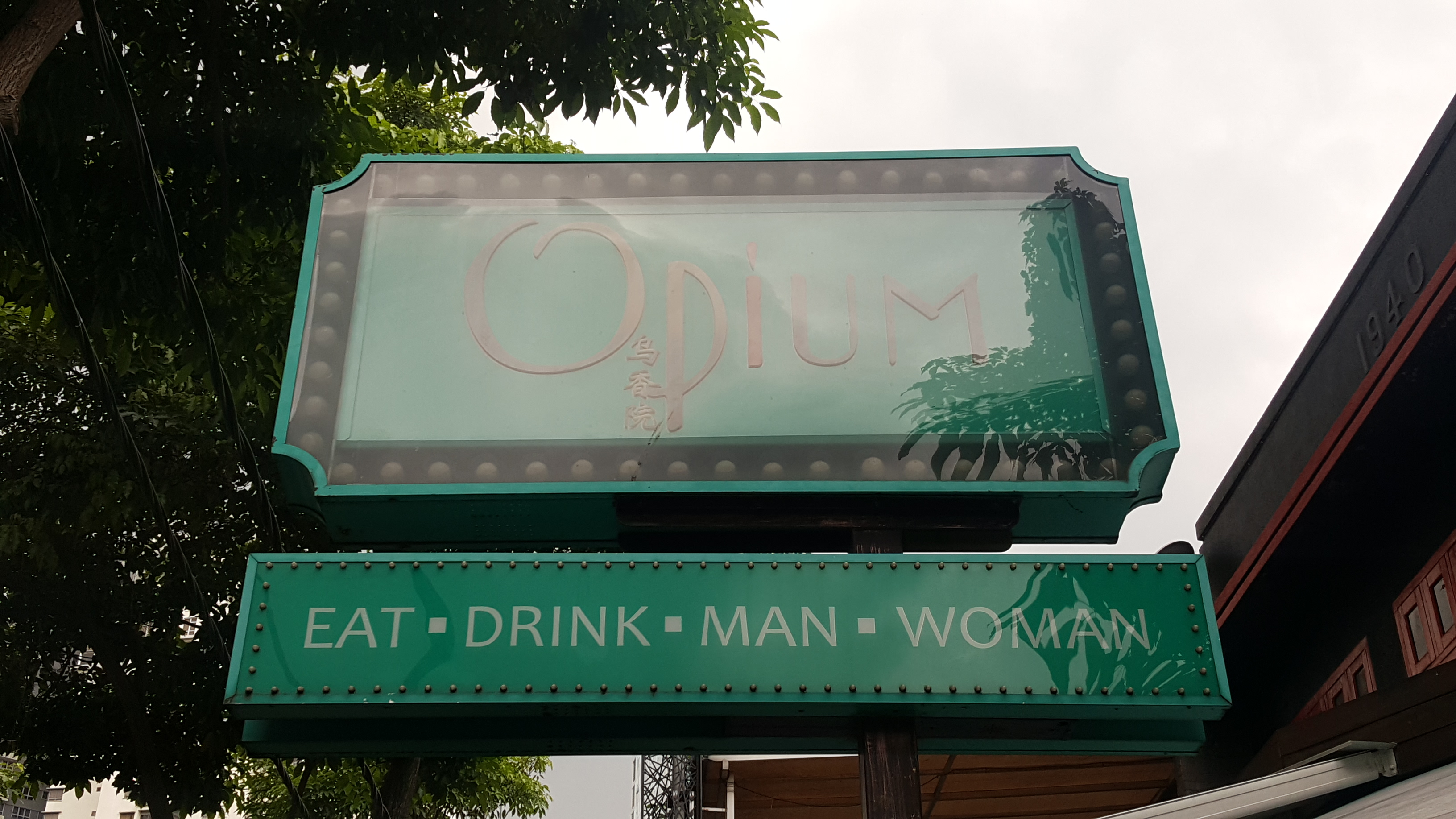A sign for a bar called Opium, with a tagline Eat, Drink, Man, Woman